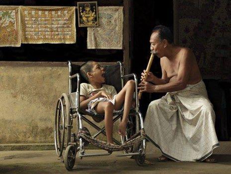 """""""Bali...egy férfi szórakoztatja a bambusz furulyájával a sérült gyermeket, aki nem az ő fia, de úgy szereti, mintha a sajátja lenne."""""""