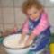 A kett éves, Kovács Noémi kisunokánk, kenyeret dagaszt.