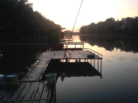 A naplementében a horgásztó Dányban egy stégről.