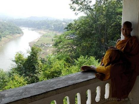 Buddhista szerzetes egy Mekong melletti templom teraszán