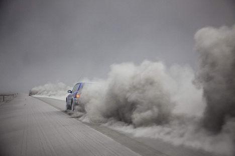 A vulkáni hamuval fedett úton haladó autók porfelhőt vernek fel az izlandi Kirkjubcjarklaustur közelében