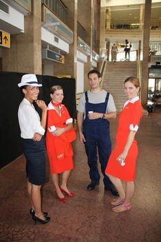 """Orosz stewardessek, amerikai repülőtéri check-ines kisasszony és """"amerikai"""" reptéri karbantartó."""